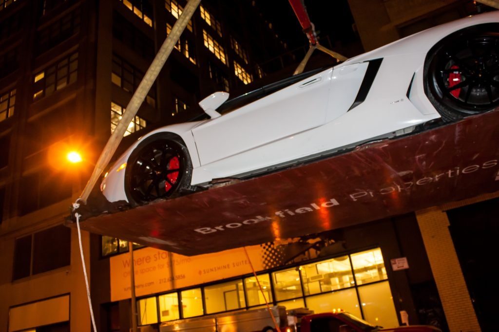 White Lamborghini Being Lifted on Platform